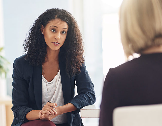 Shot of a young therapist speaking to a couple during a counseling session